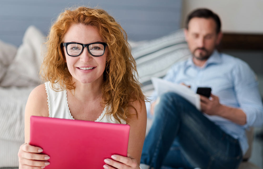 Smiling ginger woman holding tablet